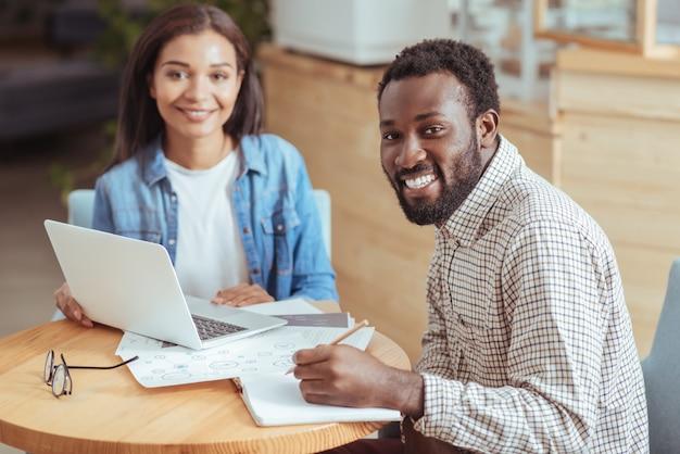 Heureux de coopérer. joyeux jeunes collègues assis à la table dans le café et travaillant sur leur projet commun tout en souriant à la caméra au sens large