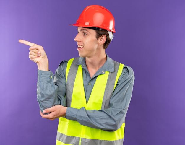 Heureux à côté d'un jeune constructeur en uniforme points à côté isolé sur mur bleu avec espace de copie