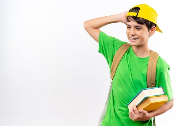 Heureux à côté d'un jeune écolier portant un sac à dos avec une casquette tenant des livres isolés sur un mur blanc avec un espace pour copie