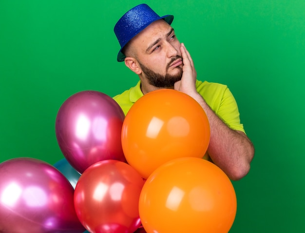 Heureux à côté jeune homme portant un chapeau de fête debout derrière des ballons mettant la main sur la joue