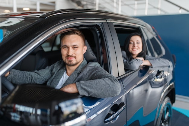 Heureux couple achetant une nouvelle voiture dans la salle d'exposition, départ du salon.