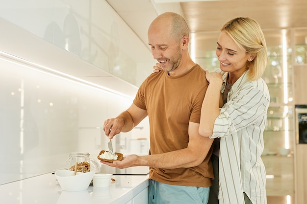 Heureux couple adulte cuisine petit-déjeuner sain ensemble en se tenant debout dans l'intérieur de la cuisine moderne