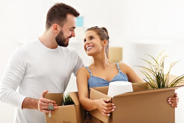 Heureux couple adulte déménageant ou emménageant dans une nouvelle maison
