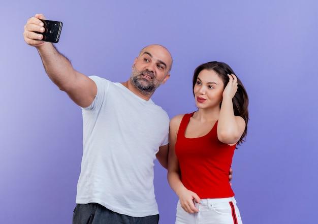 Heureux couple adulte prenant selfie homme mettant la main sur la taille de la femme et elle touche la tête