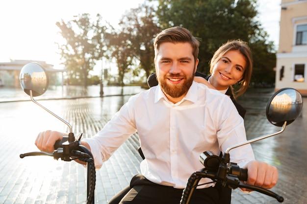 Heureux couple d'affaires monte sur une moto moderne à l'extérieur