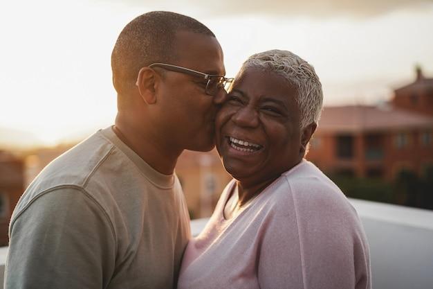 Heureux couple africain ayant un moment tendre à l'extérieur au coucher du soleil d'été - focus sur le visage de la femme