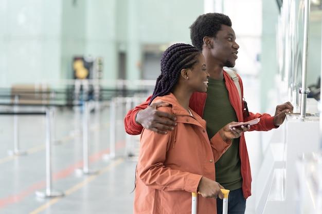 Heureux couple africain avec passeports étrangers et cartes d'embarquement debout au comptoir d'enregistrement de l'aéroport