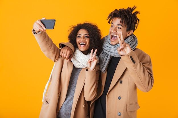 Heureux couple africain portant des vêtements d'hiver debout isolé, prenant un selfie