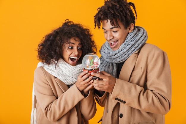 Heureux couple africain portant des vêtements d'hiver debout isolé, tenant une boule à neige
