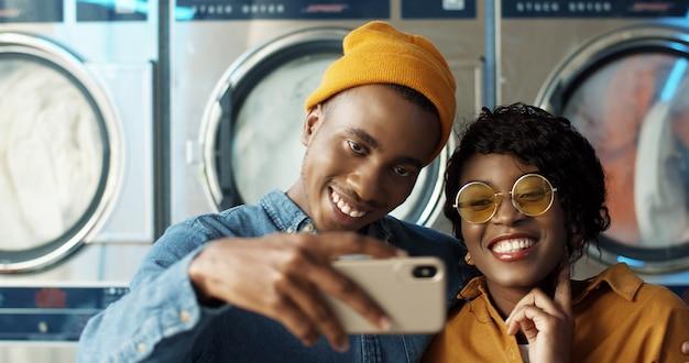 Heureux couple afro-américain amoureux étreignant et souriant à la caméra du smartphone tout en prenant une photo de selfie au service de blanchisserie. gai jeune homme et femme faisant des photos sur le téléphone aux machines à laver.