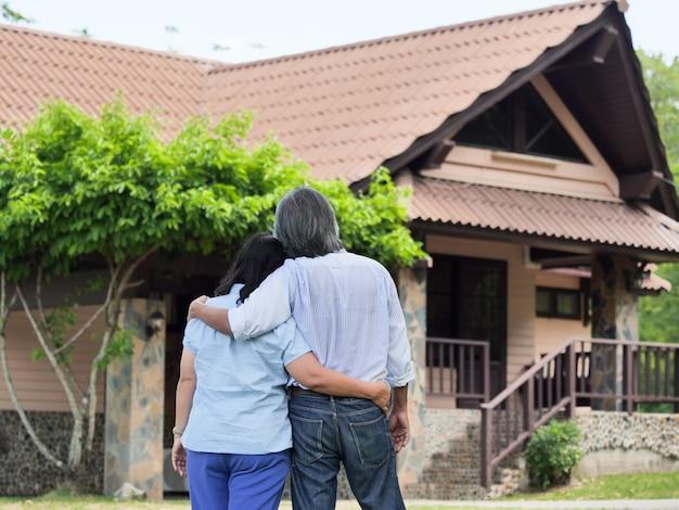 Heureux couple âgé asiatique souriant debout devant la nouvelle maison.