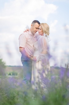 Heureux couple d'âge moyen, embrassant et profitant de moments romantiques ensemble dans le champ de lavande