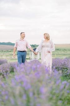 Heureux couple d'âge moyen marchant dehors dans le champ de floraison de lavande