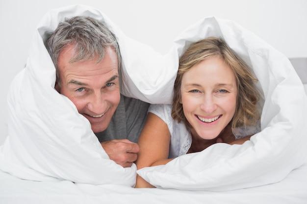 Heureux couple âgé moyen sous la couette