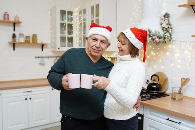 Heureux couple d'âge mûr prenant son petit déjeuner dans la cuisine de noël à la maison