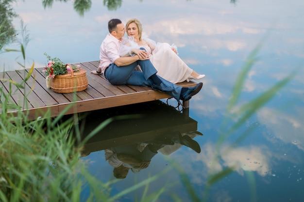 Heureux couple d'âge mûr romantique assis sur un pont en bois près d'un lac ou d'un étang à l'extérieur, s'embrassant et profitant de leur rendez-vous. célébration d'anniversaire de mariage