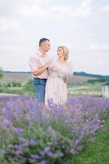 Heureux couple d'âge mûr romantique, posant ensemble en se regardant, au beau champ de lavande