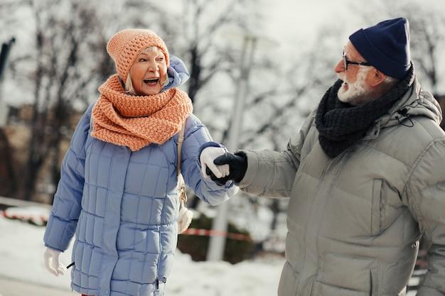 Heureux couple âgé se tenant la main et s'appuyant les uns sur les autres tout en étant sur la patinoire