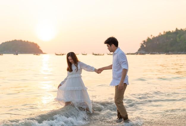 Heureux couple aller voyage de noces sur la plage de sable tropicale en été