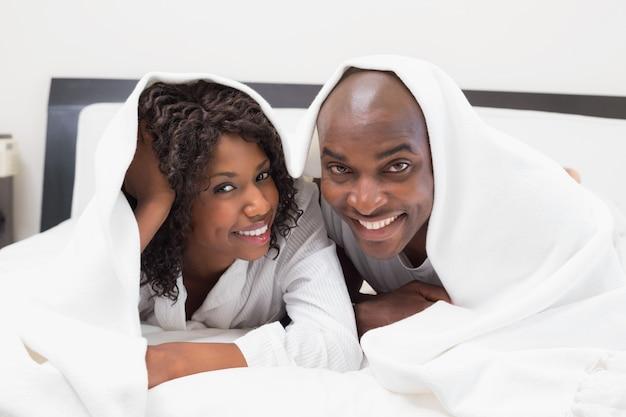 Heureux couple allongé sur le lit ensemble sous la couette