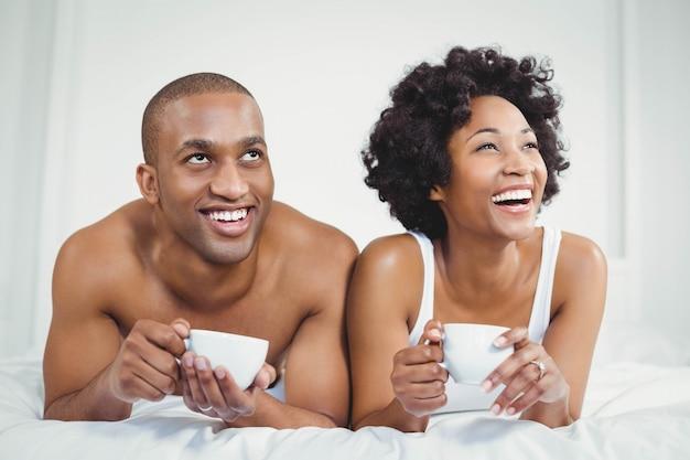 Heureux couple allongé sur le lit tout en tenant des tasses et levant