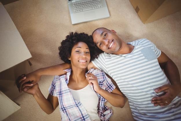 Heureux couple allongé sur le sol et souriant à la caméra