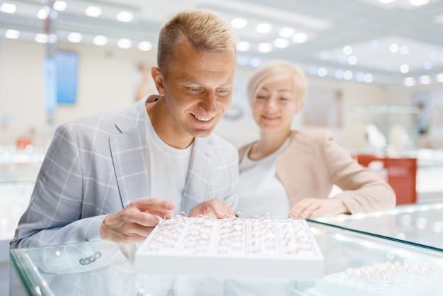 Heureux couple amoureux acheter des alliances dans une bijouterie. homme et femme choisissant la décoration en or. futurs mariés en bijouterie