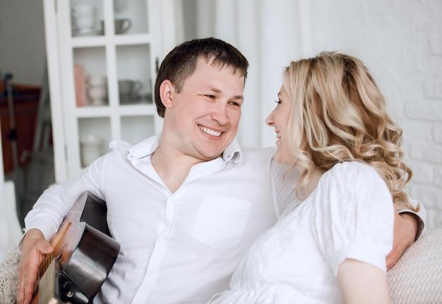 Heureux couple d'amoureux assis sur le canapé