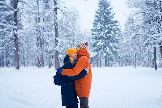 Heureux couple d'amoureux dans la forêt d'hiver enneigé