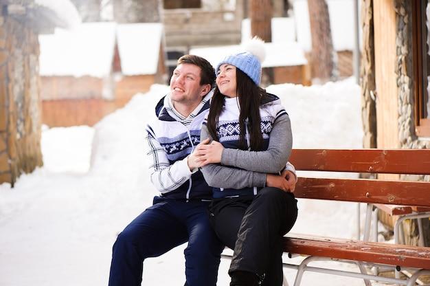 Heureux couple amoureux étreindre et s'embrasser à la station d'hiver