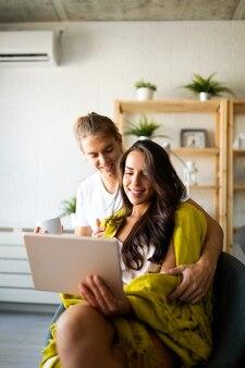Heureux couple amoureux étreindre et utiliser une tablette ensemble à la maison