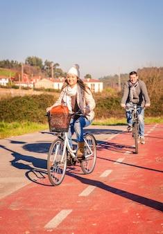 Heureux couple amoureux faire du vélo par la nature par une journée d'hiver ensoleillée