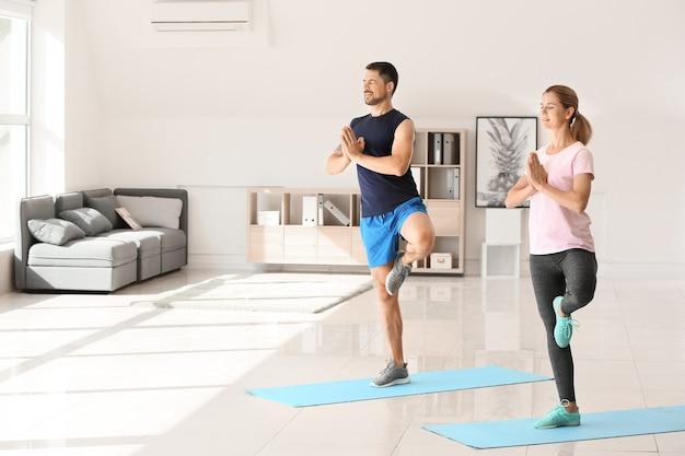 Heureux couple amoureux, faire du yoga à la maison