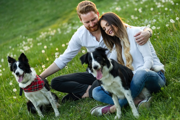 Heureux couple amoureux jouant avec des chiens dans le parc en plein air
