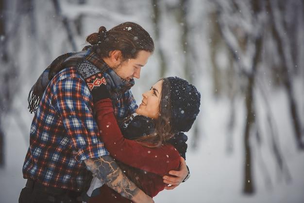 Heureux couple d'amoureux marchant dans la forêt enneigée