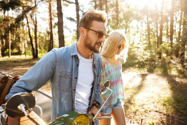 Heureux couple d'amoureux marchant avec scooter à l'extérieur