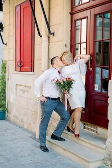 Heureux couple d'amoureux mature, debout à l'extérieur de la ville, près de la belle porte rouge vintage