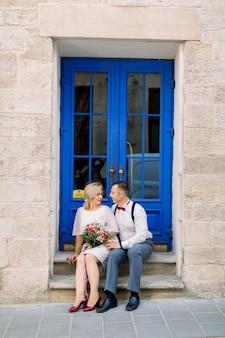 Heureux couple d'amoureux mature, embrassant à l'extérieur de la ville, assis près de la belle porte bleue vintage