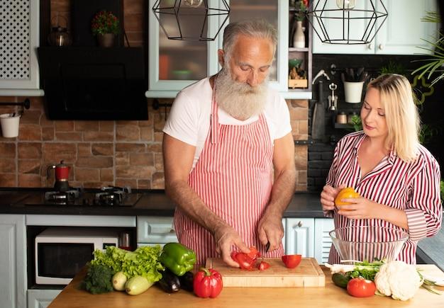 Heureux couple d'amoureux mature famille debout à la cuisine et cuisine salade.