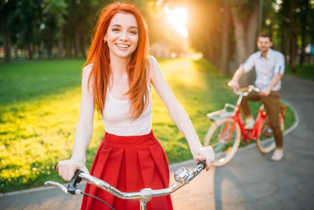 Heureux couple amoureux monte sur des vélos rétro dans le parc d'été au coucher du soleil. un rendez-vous romantique