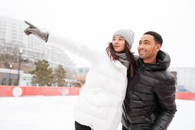 Heureux couple d'amoureux patinant à l'extérieur de la patinoire.
