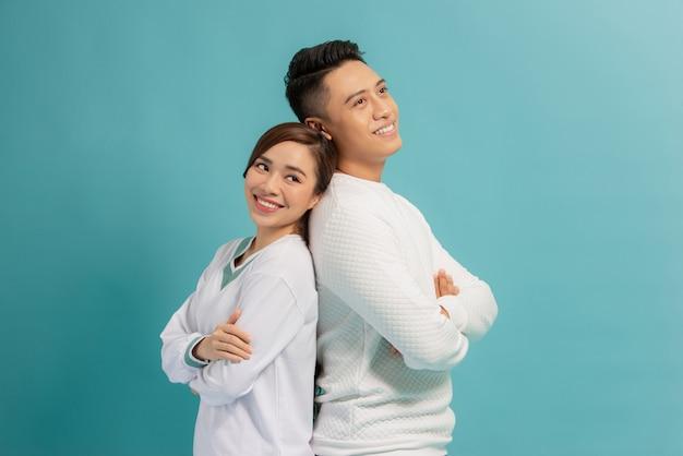 Heureux couple d'amoureux. photo de studio de beau jeune couple debout dos à dos et souriant
