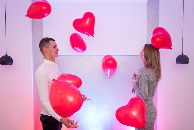 Heureux couple amoureux posant avec des ballons à air rouge en forme de coeur