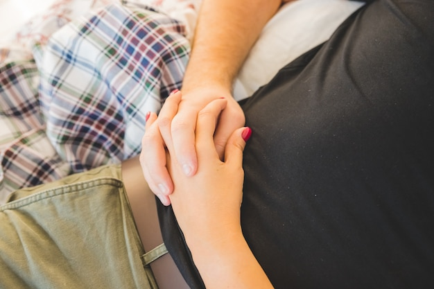Heureux couple d'amoureux profitant du temps au lit. amour, tendresse., vraie passion., mains, de, a, mâle, étreindre, sien, petite amie., couple romantique, aimer, millénaire, affectueux, femme, toucher, homme, sentiment