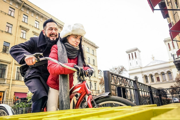 Heureux couple amoureux profitant de l'heure d'hiver en plein air sur vélo vintage