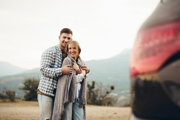 Heureux couple d'amoureux randonnée et étreinte dans les montagnes