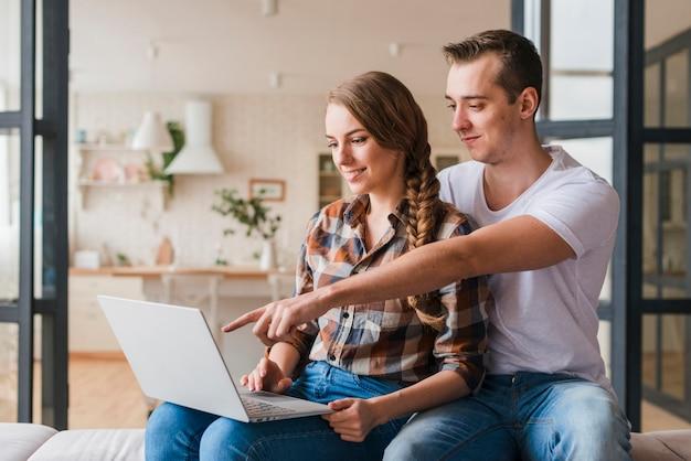 Heureux couple amoureux à la recherche sur un ordinateur portable