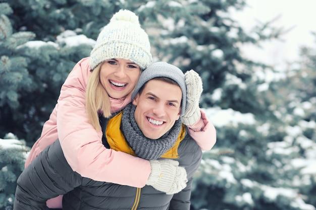 Heureux couple d'amoureux s'amusant dans le parc d'hiver