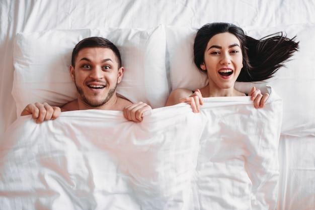 Heureux couple amoureux se trouve sur un grand lit blanc, vue de dessus. partenaires intimes souriants dans la chambre, amoureux de l'intimité chaude