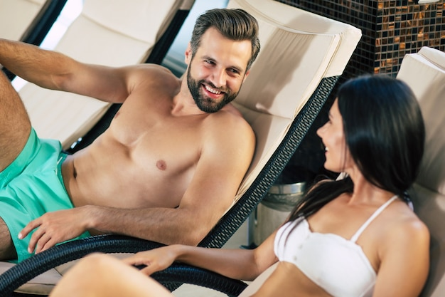 Heureux couple amoureux sur la station. beau jeune homme macho avec une belle femme mince sont allongés sur les chaises longues dans le grand centre de spa avec piscine et se parlent